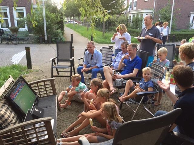 bewoners buiten rond een voetbalwedstrijd op tv