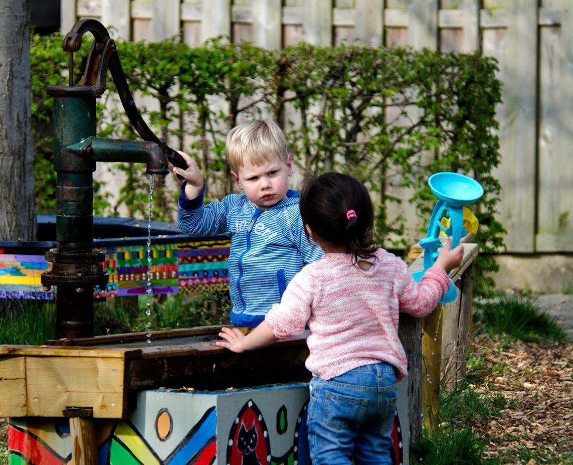 kinderen spelen met de waterpomp