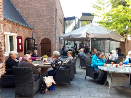 mensen buiten aan tafels seniorendag