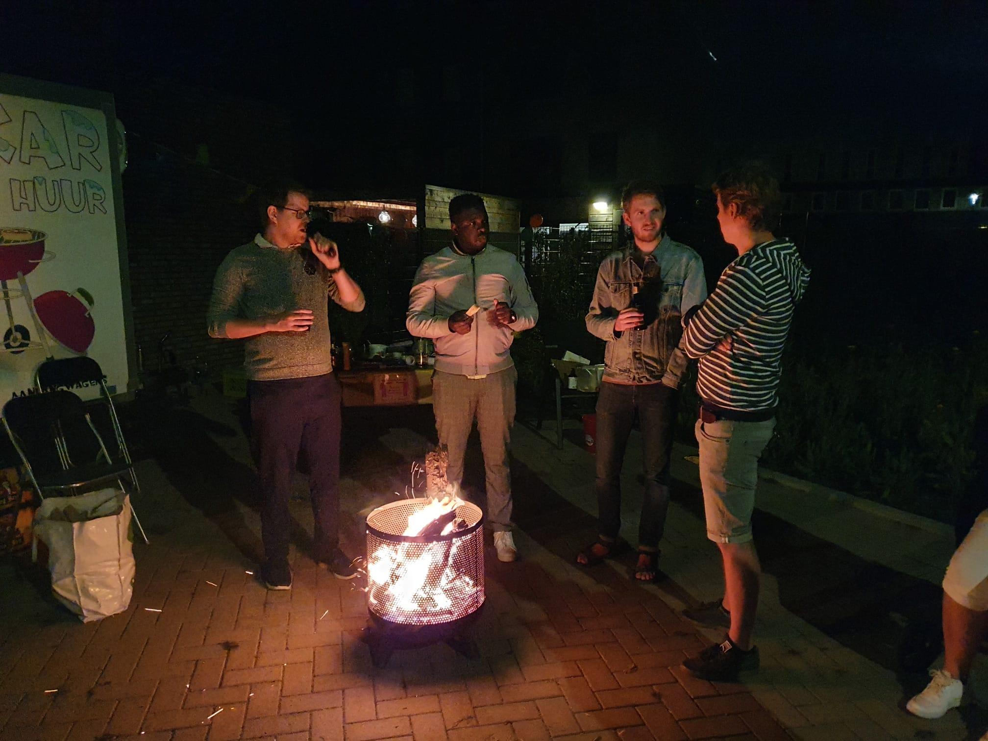Mensen staan rond een vuurkorf in het donker
